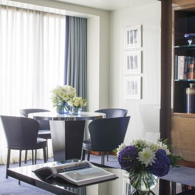 Ambassador Suite Lounge with navy decor and a table with 4 chairs by the window in the Four Seasons Hotel, Park Lane, London