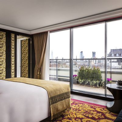 Red and Gold decorated bedroom overlooking the city in the the L'oscar London Hotel