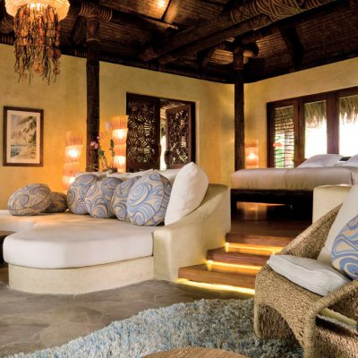 Bed with stairs leading to the Lounge area of an open plan bedroom in the Laucala Island Resort – Fiji
