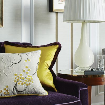 Purple and grey sofas with bright floral patterned cushions sit aside a table in a Suite in the Marriott Hotel, Park Lane, London with