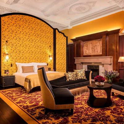A bright orange and brown decor bedroom with a bed and an old fashioned fireplace in the L'oscar London Hotel.